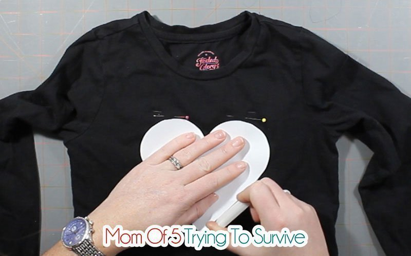 tracing a heart template onto black shirt with tailors chalk